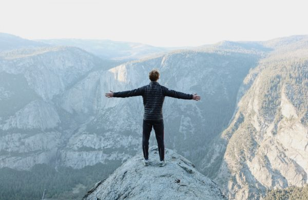 man opening his arms wide open on snow covered cliff with view of mountains during daytime